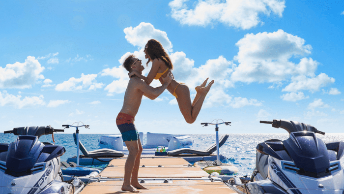 young couple in bathing suites on OCEAN CLUB 164' Trinity boat review