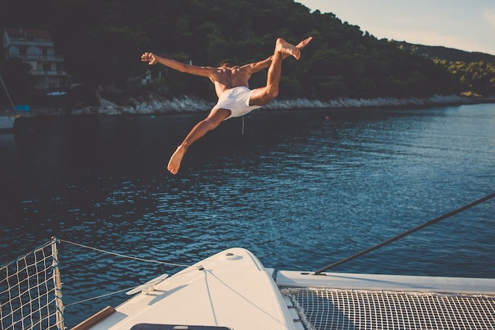 a man jumps from a boat into the water to rescue somebody, Five Steps You As A Passenger Should Take In Case Someone Goes Overboard